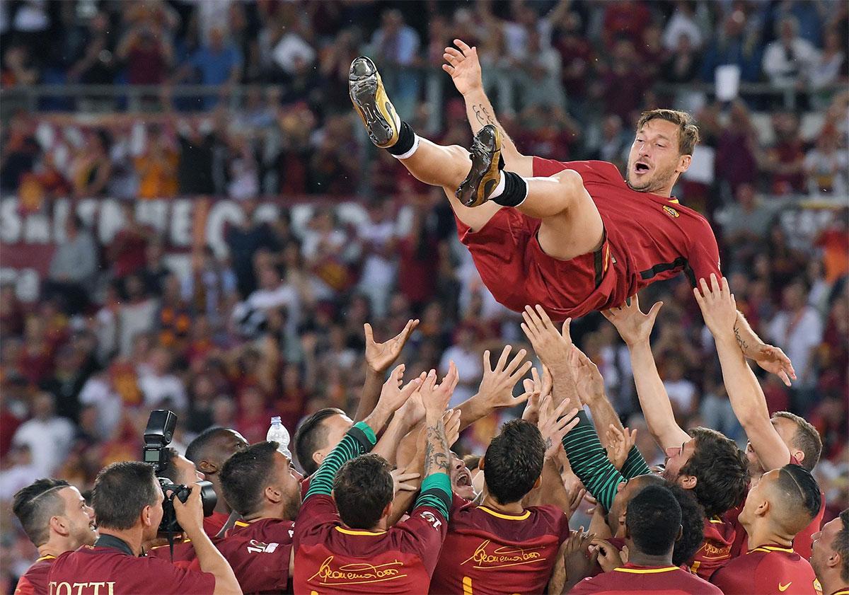 Totti lanciato in aria dai compagni di squadra durante il suo addio